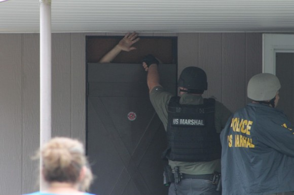 As the majoirty of the federal agents searched the second-floor of the home, the suspect came out from the carport.  Credit: Tom Sofield/LevittownNow.com